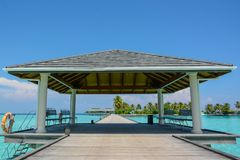 Arrival pier with a roof at the tropical island. Resort at Maldives Stock Photos