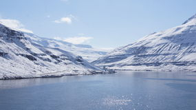 Arrival Seydisfjordur in the snow. Arrival with the ferry from Denmark to Iceland early May in Seydisfjordur when the mountains in the fjord where covered with stock photo