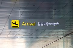 Arrival sign in english and Myanmar language with symbol of the plane landing in black on yellow color. Installed from the ceiling royalty free stock image