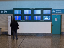 Arrivals boards in airport. Person in Milan Malpensa airport checking info boardsl Royalty Free Stock Photos