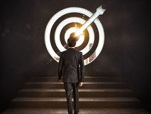 Arrive at a goal of success. Businessman climbing the stairs up to a target.. 3D Rendering Stock Photo