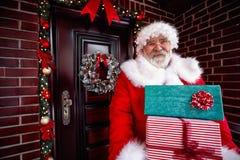 Arrives Santa Claus de sorriso e presente levando do Natal dos lotes imagem de stock royalty free