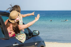 Arriving on the beach. Mother and daughter in the car arrived on the beach Royalty Free Stock Photography