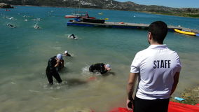Arriving at the edge of triathletes at the end of the swim leg. End of tour to swim in a triathlon with a member of staff in the foreground stock video