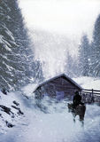 Arriving home. Cowboy and his horse into a snowy and windy landscape, arriving to a log cabin Royalty Free Stock Images