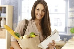 Arriving at home. Happy woman arriving at home with shopping bag and mail, smiling stock photo