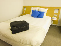 Arriving at the hotel room. Suitcase on the bed of a hotel as a concept of travel Stock Photos