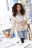 Arriving at office. Attractive office worker arriving at workplace in the morning with coffee royalty free stock photo