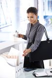 Arriving at the office in the morning. Young woman arriving at the office in the morning, looking at mail, drinking coffee royalty free stock photos