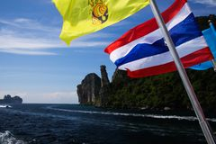 Arriving on tropical island Ko Phi Phi with ferry from Phuket - Close up of Thai flag waving from the boat with rocky coast line stock photo