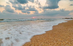 Arriving wave on the beach at sunset on windy day Royalty Free Stock Photography