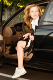 Arriving at work. Attractive blond caucasian business woman getting out of car wearing sneakers holding high heel shoes and briefcase stock photography