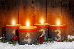 4 Arrivo, candele d'ardore con i numeri davanti a backg di legno Immagini Stock