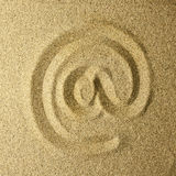Arroba handwritten in the sand. Golden colors Royalty Free Stock Images