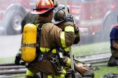 Arrodillamiento de dos bomberos Imagenes de archivo