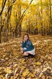 Arrodillamiento femenino joven en Forest Trail Foto de archivo