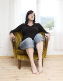 Arrogance. Woman with an arrogant expression sitting on chair Stock Images