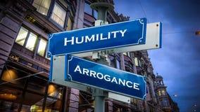 Arrogans för ödmjukhet för gatatecken kontra royaltyfria bilder