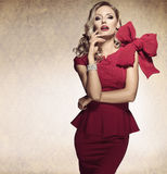 Arrogant blond sexy girl. red dress. Sophisticated elegant lady in red dress with a big bow and jewellery looking in camera with arrogant expression Stock Images