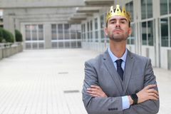 Arrogant businessman with a crown in office space.  stock photography