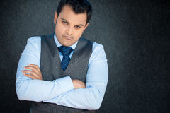 Arrogant. Closeup portrait, displeased, angry, grumpy business man, bad attitude, arms crossed, folded, looking at you, gray black background. Negative human stock images