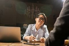 Asian lady working with colleague in dark office royalty free stock photography