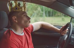Arrogant driver. Arrogant driver man with golden crown above his head. Disdainful and boorish attitude on the road concept royalty free stock image