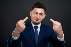 Arrogant lawyer rising both middle fingers. On a dark background royalty free stock photo