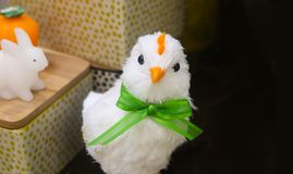 Arrogant looking white decrative easter chick with green bow with baskets and toy bunny in background - room for copy stock photos