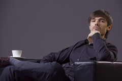 Arrogant male. Portrait of arrogant male sitting in chair with cup coffee Royalty Free Stock Photography