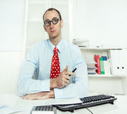 Arrogant man sitting at desk with glasses, a red tie and a blue. Shirt working at an insurance or bank - know-it-all Royalty Free Stock Photo