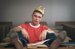 Student. Arrogant student boy with golden crown above his head with an insolent look sits at a desk. Bad behavior in school concept stock photos