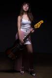 Arrogant teenage girl in shadow holding guitar Royalty Free Stock Image