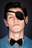 Arrogant young  man. In the piratical eye-band and bow tie Royalty Free Stock Photo
