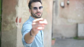 Arrogant young man fixing his shirt`s collar and snapping his fingers. While inviting you to follow him for a walk on the street of an old town stock video footage