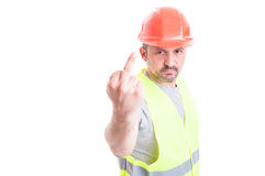 Arrogant young workman or builder showing an obscene gesture Royalty Free Stock Images
