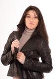 Arrogante brunette in een leerjasje Stock Afbeeldingen