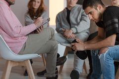 Arroganter Jugendlicher, der bei einer Sitzung des Stützungskonsortiums während hallo sitzt lizenzfreies stockbild