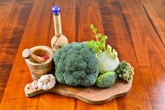 Arrolhe a garrafa, almofariz de madeira verde-oliva, vegetais verdes, brócolis, erva-doce, alho Fotos de Stock
