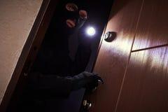 Arrombamento de um apartamento Ladrão na máscara com lanterna elétrica imagens de stock