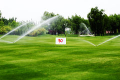 Arrosage de terrain de golf photographie stock