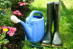 Arrosage et gumboots bleus Image stock