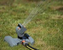 Arroseuse de oscillation d'irrigation de la pelouse au plan rapproché de midi Photographie stock libre de droits