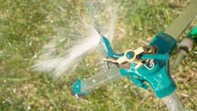 Arroseuse de yard sur l'eau de propagation fonctionnante de trépied au-dessus de l'herbe au-dessus du slomo de vue clips vidéos