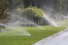 Arroseuses de l'eau arrosant la pelouse en parc Image stock