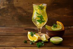 Arrosez avec la chaux, le citron et les feuilles en bon état sur un fond en bois foncé images stock