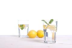 Arrosez avec le citron et la menthe dans un verre sur la vue de côté de table d'I photographie stock