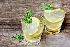 Arrosez avec les citrons frais dans des verres sur la table Images libres de droits
