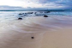 Arrosez dans le mouvement lent sur une plage sablonneuse Images stock