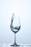 Arrosez l'éclaboussement du verre à vin avec de l'eau plus propre tout en se tenant sur le verre des gouttelettes sur le fond lég Image stock